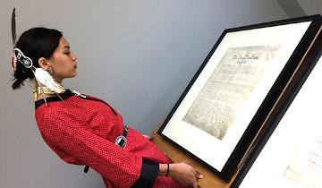 Miyopin Cheechoo, looking at the first page of the written treaty document at the Treaties 1 - 11 National Gathering at Taykwa Tagamou Nation, August 2017. Photo taken by Christina Nielsen